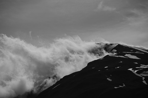 Clouds rise like smoke from a ridge.