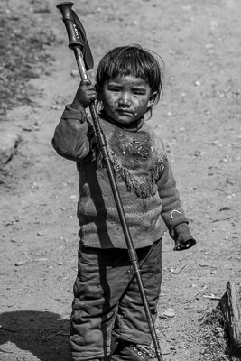 Borrowing a hiking pole, young boys play with travelers, Gho, Tsum Valley